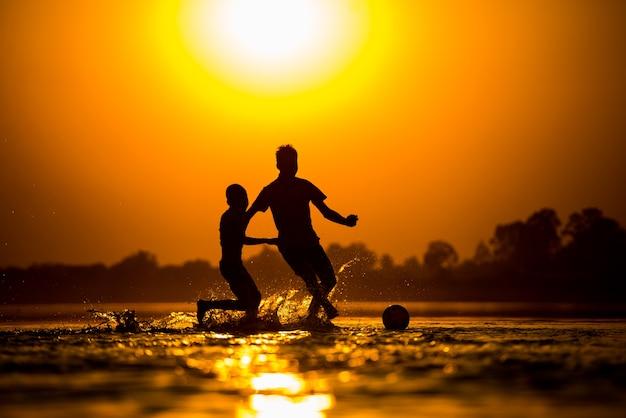 Силуэт детей, играющих в футбол на пляже