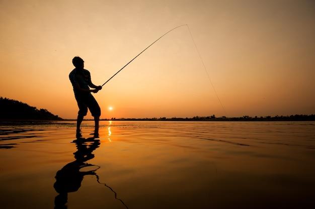 Силуэт человека, ловившего рыбу в реке