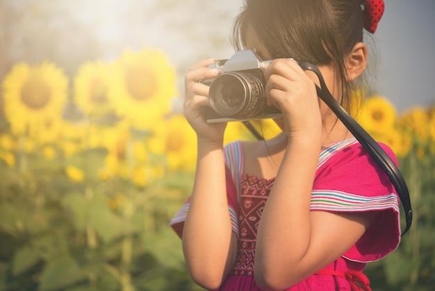 Милая маленькая девочка фотографирует с винтажной камерой в поле солнцецвета.