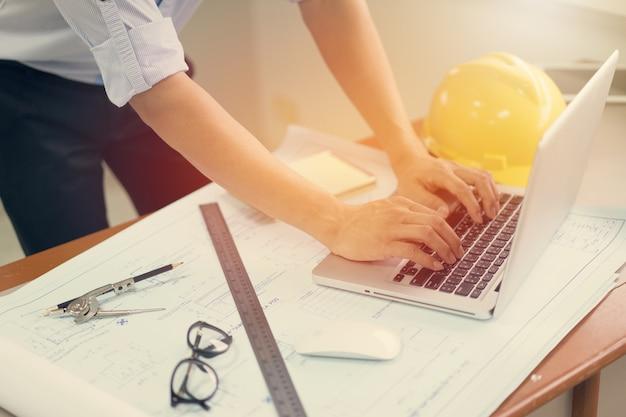 建設プロジェクトのスケッチのラップトップと青写真を扱うエンジニア男