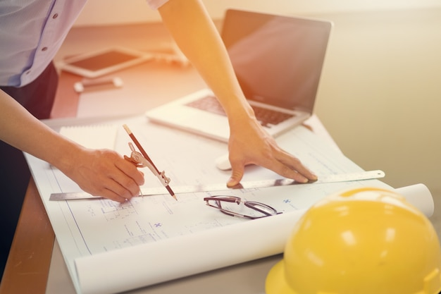 エンジニアリング男と建設プロジェクトのスケッチのラップトップと青写真の操作