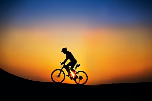 Силуэт велосипедиста с горным велосипедом на красивом времени захода солнца.