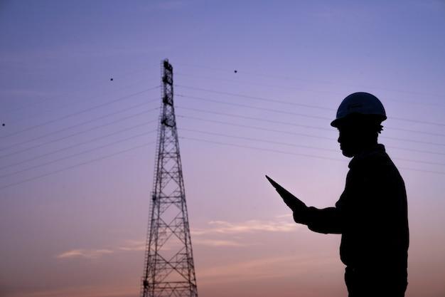 高電圧ポストで安全に作業するための建設作業員のための無線による技術者立って注文のシルエット。仕事と仕事における産業と安全。