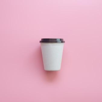 Плоский дизайн лежал чашка горячего кофе на розовой пастели.