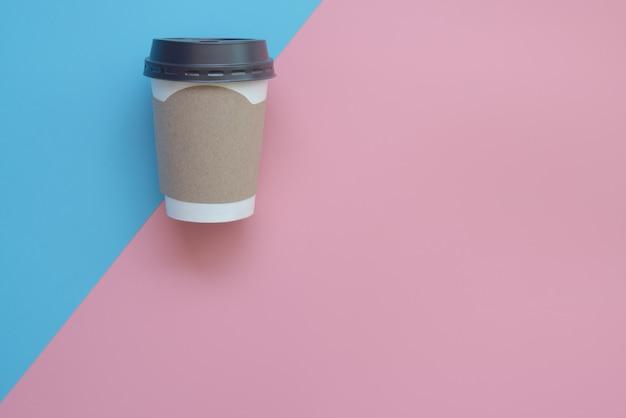 Плоская планировка с чашкой горячего кофе с чистым картоном для вашего бренда на розово-синей пастели.