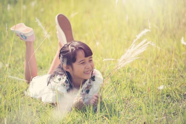 Милая счастливая девушка лежа на траве.