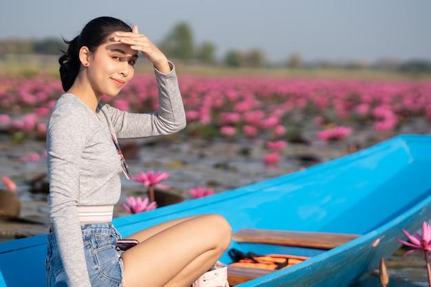 朝はピンクの蓮の湖で青いボートで美しい少女。日焼け止め。