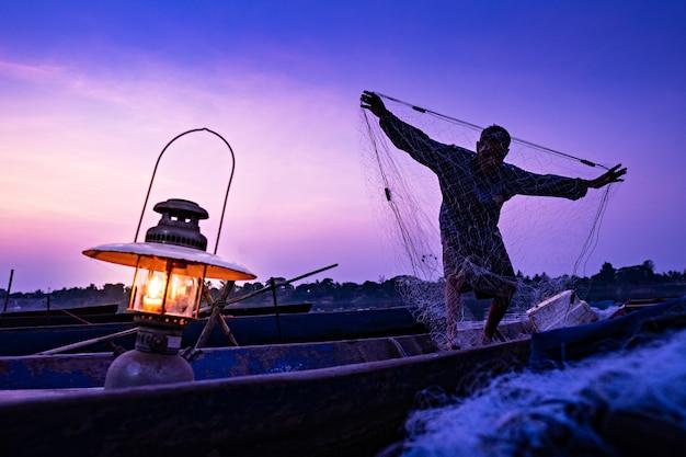漁師は夕方にボートに取り組んでいます。