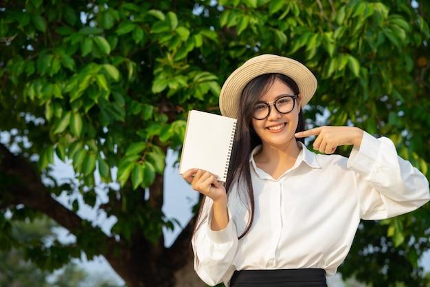 Счастливая девушка держит пустой блокнот с природой