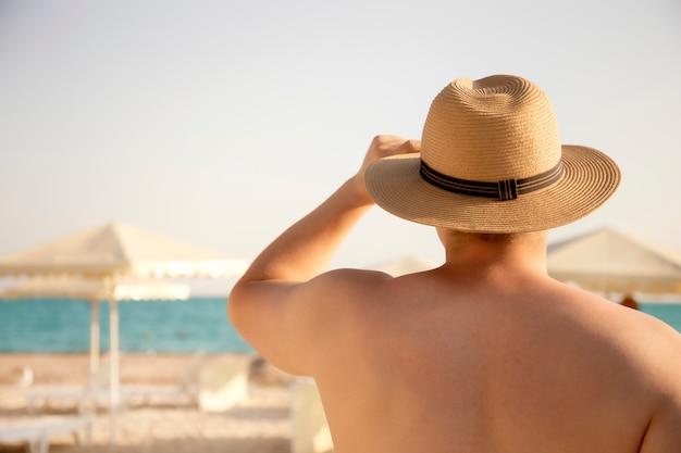 海を見て帽子の若い魅力的な筋肉男
