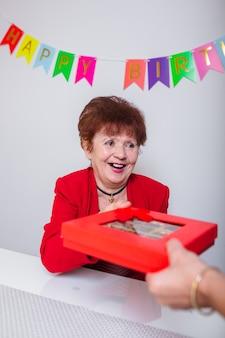 高齢の女性は贈り物を受け取ります。
