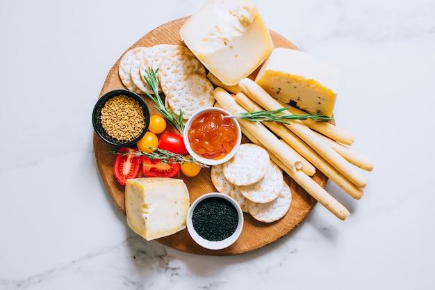 トマト、ジャム、バゲット、パンスティック、クラッカーを入れたチーズボード