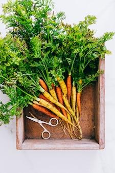 大理石の背景に木製のボックスに根が新鮮な汚れた野菜のニンジン