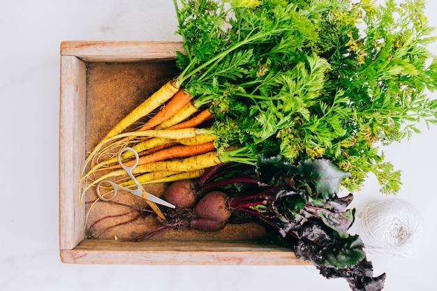 根は大理石の背景に木箱の新鮮な汚れた野菜のニンジンとビート