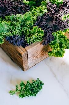 大理石の背景に木製の箱で新鮮なケール