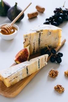 古い英語スティルトンチーズ。ブルーチーズ、イチジク、ブドウ、大理石のまな板の上