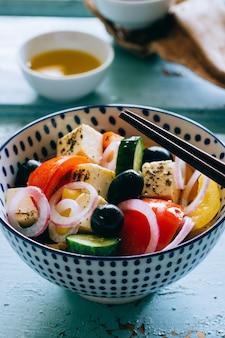 野菜のサラダとオリーブの木製の青い背景上の箸