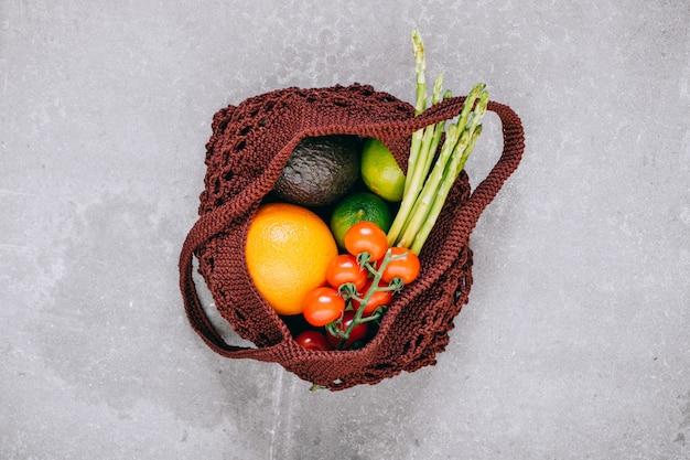 大理石の背景に生野菜の生分解性ショッピングバッグの静物