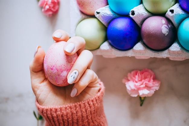 女の子はスタンド、ピンクと大理石の背景にピンクのイースターエッグを持っています。