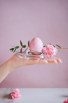 女の子はスタンド、ピンクと大理石の背景、ミニマリズム、花にピンクのイースターエッグを持っています。