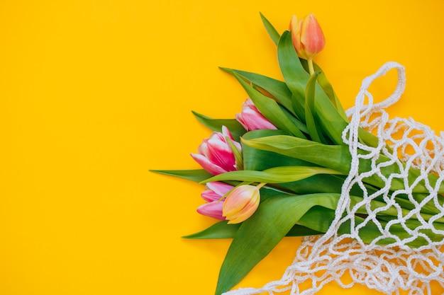 黄色の背景にエコバッグの色とりどりのチューリップの春の花束。コピースペース、フラットレイアウトの背景。