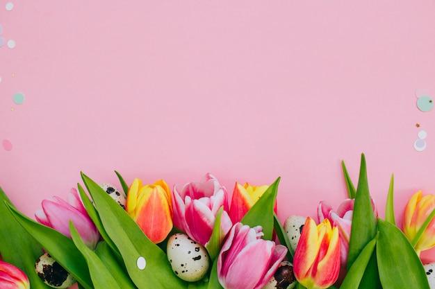 イースターのコンセプト、金色の星飾り、鮮やかな紙吹雪と色とりどりのチューリップとピンクの背景にウズラの卵。