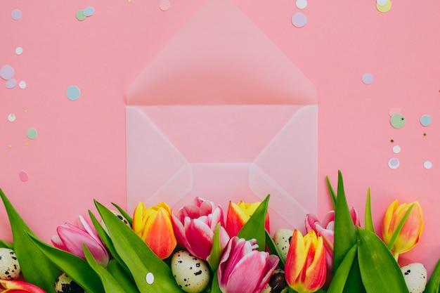 イースターのコンセプト、金色の星飾り、鮮やかな紙吹雪とオープンマットの透明な封筒