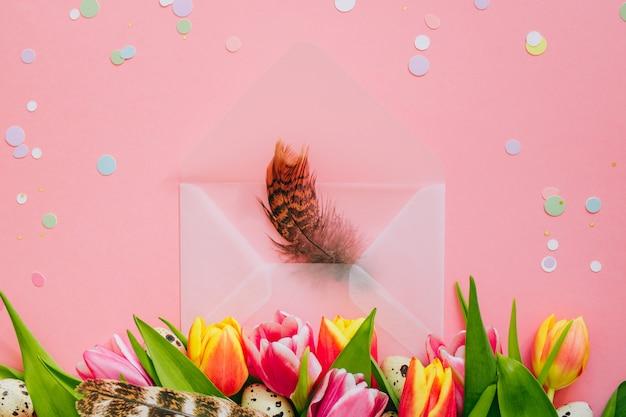 イースターの概念、紙吹雪と羽、チューリップとウズラの卵ピンクの背景に開いたマット封筒