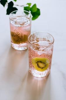 大理石、緑のツタ、明るい太陽の下でクリスタルグラスにピンクのワイングラス