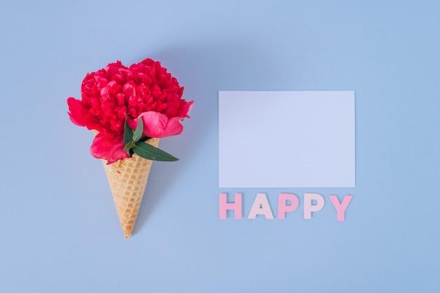 青と白の明確な空白の上にピンクの牡丹とフラットレイアウトアイスクリームコーン。