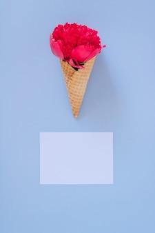 青と白の明確な空白の上にピンクの牡丹とフラットレイアウトアイスクリームコーン。ハッピーテキスト