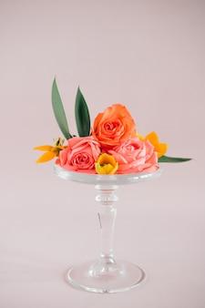 ガラスケーキの上のカラフルな熱帯の花の組成はピンク、トレンド組成の上に立つ