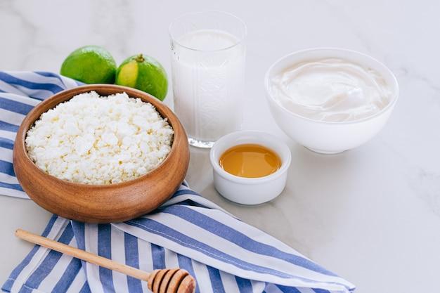 カッテージチーズの健康的な朝食、サワークリーム、蜂蜜、ライム、大理石のテーブル