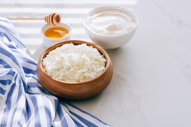 カッテージチーズの健康的な朝食、サワークリームと大理石のテーブルの上に蜂蜜