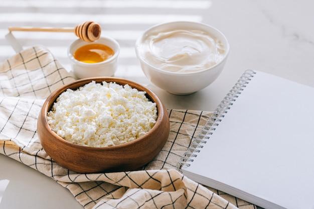 カッテージチーズのサワークリームと蜂蜜の健康的な朝食、あなたのテキストのきれいな空白、大理石のテーブルのダイエット計画