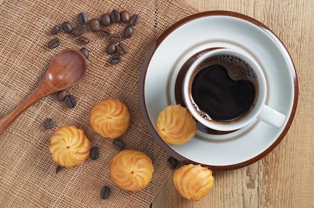 一杯のコーヒーと木製のテーブル、上面に小さなカスタードケーキ