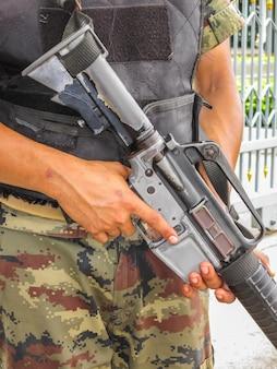 Солдат держит пулемет.