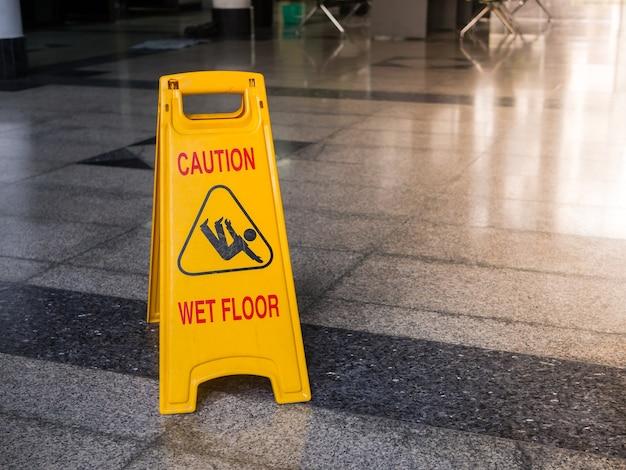 Желтый знак, предупреждающий о влажном полу.