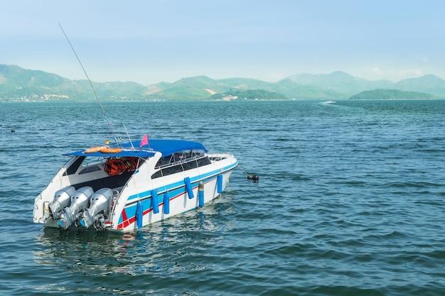山の背景と海で白いスピードボート。