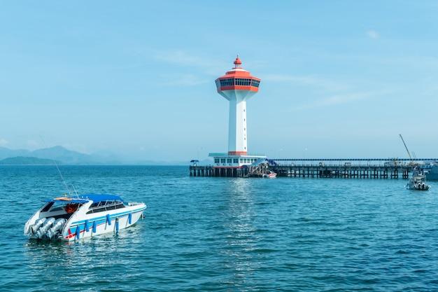 旅行のための青い海のスピードボートと白とオレンジの灯台。