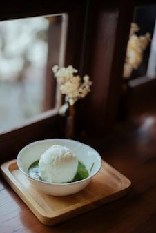 木のテーブルに抹茶が入ったアイスクリームは、和風のように見えます。