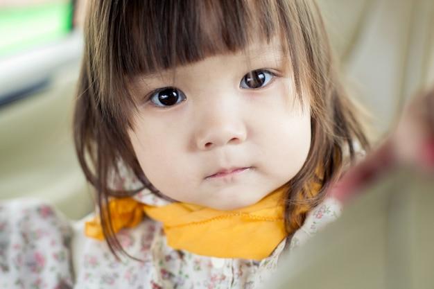 Маленькая девочка в машине показывает свое серьезное выражение лица