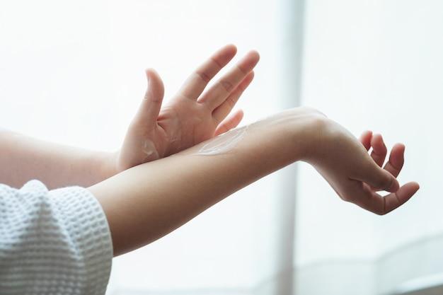 Женщина в халате наносит увлажняющий крем для рук