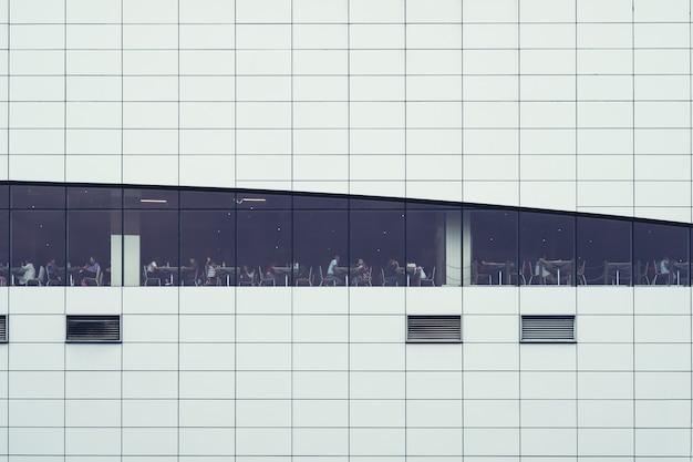 Люди сидят в здании столовой. окна интерьерные. концепция для занятости, бизнеса, корпоративного, отдыха, деловых людей, современной жизни, занятых людей