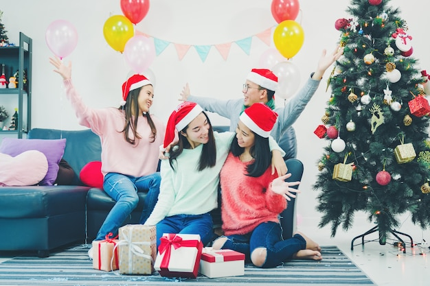 素敵に飾られたクリスマスツリーの隣に座っている若い友人のグループ