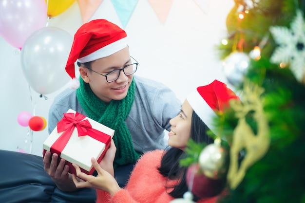 Портрет двух брюнеток волосатая романтическая пара дать новогодний рождественский подарок своей даме, сидя на диване диван в декоративном доме в помещении