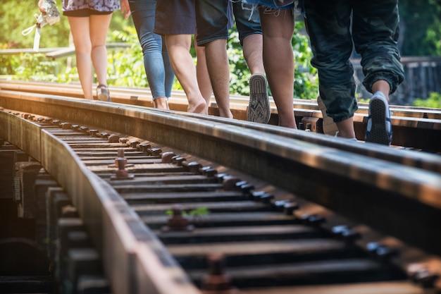 人々は、死の鉄道で暖かい日光の下で鉄道を歩いています。