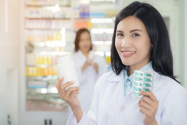 薬剤師は彼女の手で錠剤のパケットを保持しています。