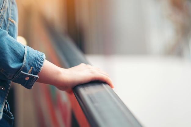 Точка зрения женщины, едущей на эскалаторе на второй этаж торгового центра. одна рука видна в рамке, держащей рельс эскалатора.