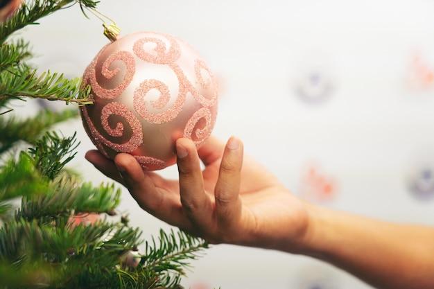 クリスマス、クリスマスツリーブランチのツリーを飾る手のホールドボールのクローズアップ